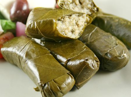 delectable: Greek dolmas wrapped with vine leaves and rice with salad. Stock Photo