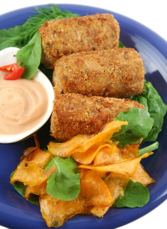 Crumbed tuna croquettes with sweet potatoes and a rocket salad. photo