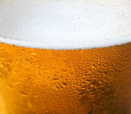 Close up background of a foaming glass of beer. photo