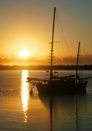 Daybreak through clouds over an old ketch. Stock Photo - 2842378