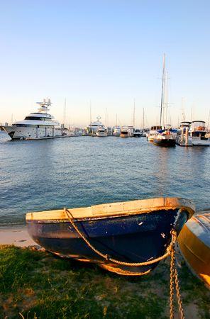 literas: Blue dinghy a la puesta del sol con la marina de yates en el fondo.  Foto de archivo