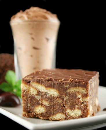 rich flavor: Chocolate slice with chocolate mousse in the background. Stock Photo