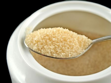 satisfying: Spoonful of raw sugar on a spoon ready for coffee.