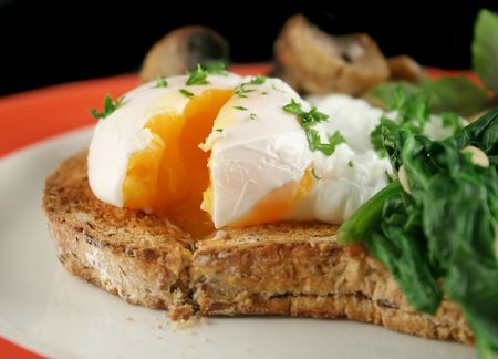 poached: Sliced poached egg breakfast with blanched spinach and pine nuts with mushrooms and shallots.