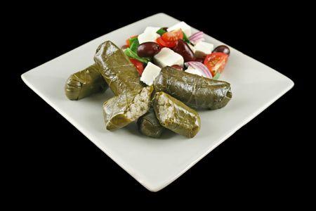 wijnbladeren: Griekse dolmades verpakt met wijn stok bladeren en rijst met salade. Stockfoto