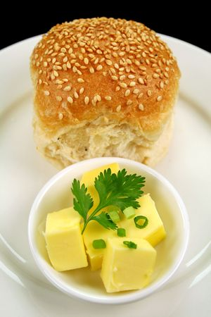 healthful: Dinner bread roll with dish of butter with green garnish. Stock Photo