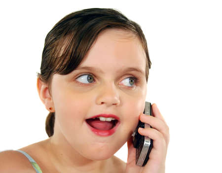 look after: Little girl with a surprised look after listening on her cell phone. Stock Photo