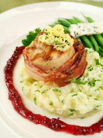 jus: Chicken fillet mignon on parsley mashed potato with green beans and blue cheese and red wine and raspberry jus. Stock Photo