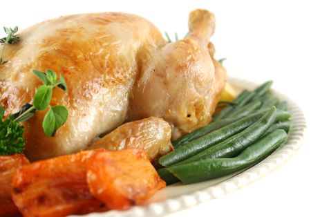 baked chicken: Whole roast chicken with potatoes pumpkin carrots and beans.