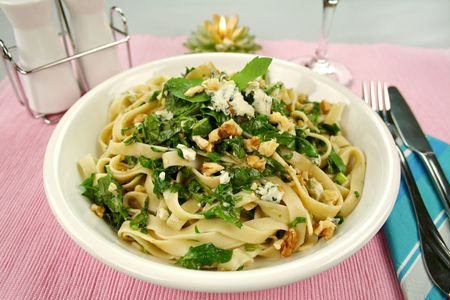Fettucini with spinach blue cheese and walnuts with a mint garnish. Stock Photo
