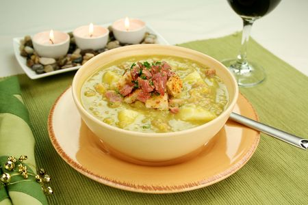 croutons: Chunky pea and ham soup with croutons and ham with a parsley garnish.