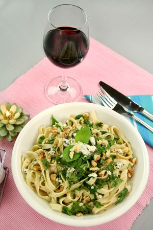 redwine: Fettucini with spinach blue cheese and walnuts with a mint garnish. Stock Photo