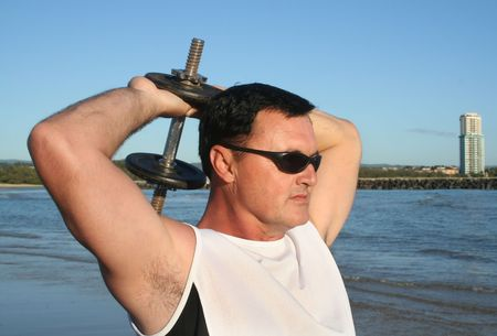 perspiring: Man works out with weights on the beach just after sunrise.