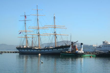permanently: The tall ship Balclutha which is permanently berthed at the Hyde Street Pier in San Francisco with Alcatraz in the background just after sunrise.. Stock Photo