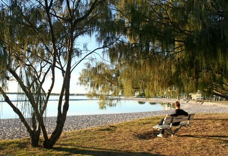 Female sitting on a bench seat by the water just after dawn. Stock Photo - 3451817