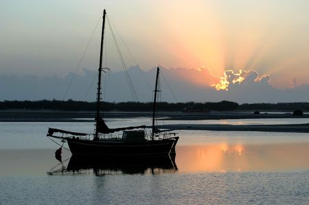 ketch: Ancient old ketch moored peacefully at sunrise.