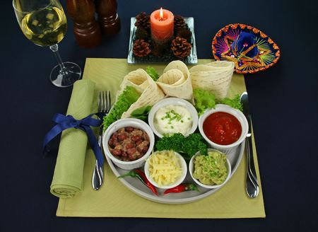 Mexican vegetarian platter with tortillas, guacamole, refried beans, cheese, sour cream and tomato salsa, photo
