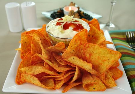 Nachos and Mexican dip topped with sour cream, salsa and grated cheese. photo