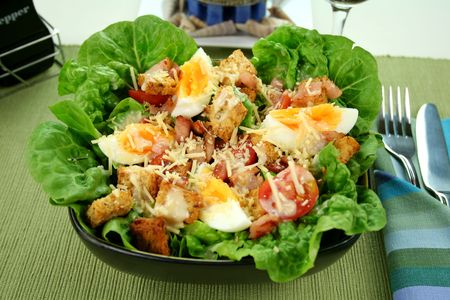 caesar salad: Fresh Caesar salad with lettuce, cherry tomatoes, parmesan cheese, egg, bacon and croutons. Stock Photo