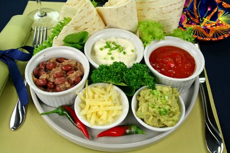 tortillas: Mexican vegetarian platter with tortillas, guacamole, refried beans, cheese, sour cream and tomato salsa
