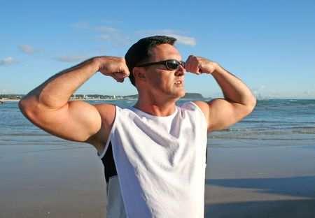 Man doing stretching and flexing exercises on the beach just after sunrise. photo