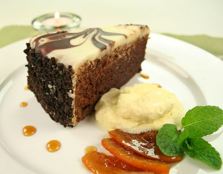 Rich chocolate cake with orange toffee and cream with a mint garnish. photo