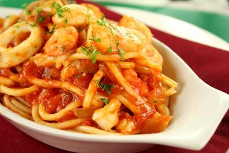 Deliziosi gli spaghetti alla marinara con pesce, gamberi, calamari e cozze con una salsa di pomodoro piccante.