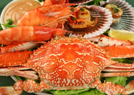 shellfish: Fresh seafood platter of cooked shrimps, sand crab and pan fried scallops and lemon.