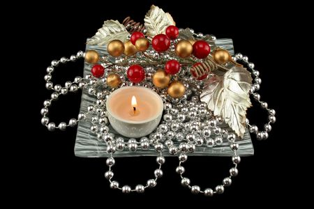 Christmas decoration made from silver necklace with berries and leaves with a candle. photo