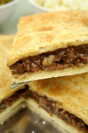 Slice of beef pie with peas and mashed potato ready to serve.