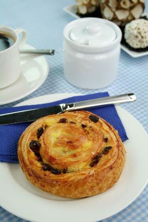 sultanas: Delicious sultana danish pastry with a cup of black coffee and sugar.