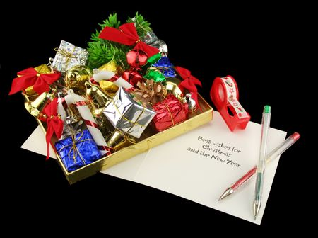 meaningful: Box of wrapped Christmas gifts and decorations with tape and pens.