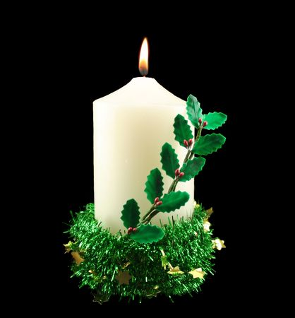 meaningful: Christmas candle alight with holly and tinsel with stars. Stock Photo