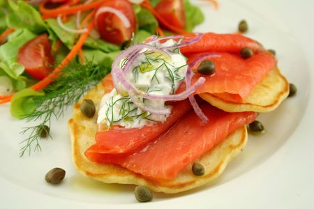 Corn fritters topped with smoked trout with dill, capers and cottage cheese. photo