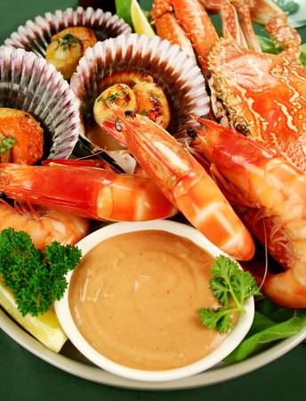 Fresh seafood platter of cooked shrimps, sand crab and pan fried scallops with coriander with Thousand Island Dressing. photo