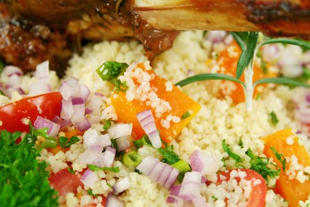 shank: Roasted lamb shank on tomato, butternut pumpkin and parsley couscous. Stock Photo