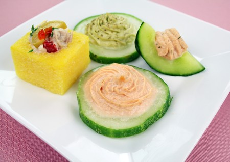 rounds: Cucumber rounds with avocado, salmon and cream cheese with a tuna polenta. Stock Photo
