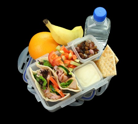 Healthy kids lunch box made up of pita bread ham and salad, fresh fruit, sultanas and drinking water. Stock Photo