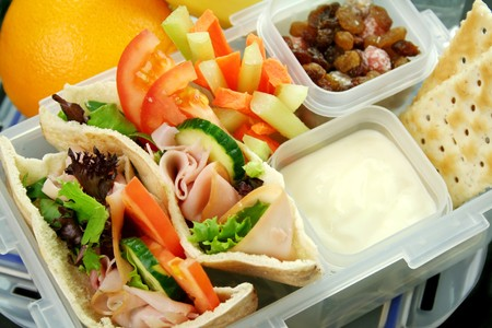 healthy lunch: Healthy kids lunch box made up of pita bread ham and salad, fresh fruit, sultanas and drinking water. Stock Photo