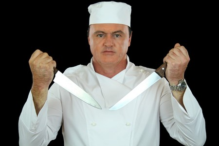 Very serious chef holding two cooking knives in a challenging position. photo