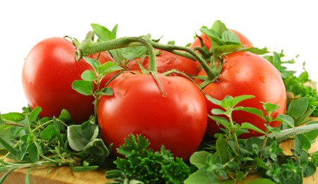 Vine ripened tomatoes on a bed of garden fresh herbs. Stock Photo