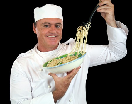 Chef lifting cooked spaghetti from a bowl with a pasta fork. photo