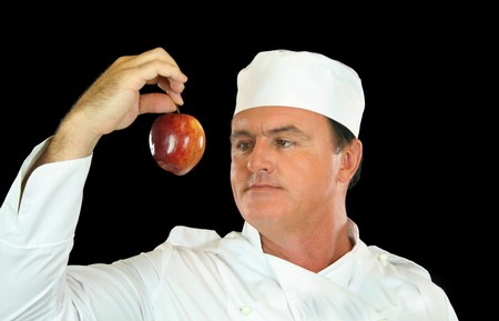 contemplates: Chef holds up healthy apple and contemplates its use.
