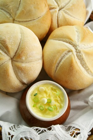 Fresh round breadrolls with a jar of butter and diced spring onions. photo