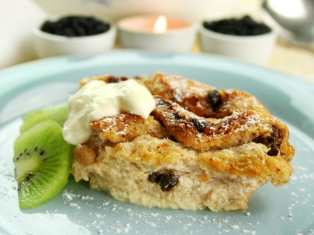 Delicious bread and butter pudding dessert with kiwi fruit and cream.