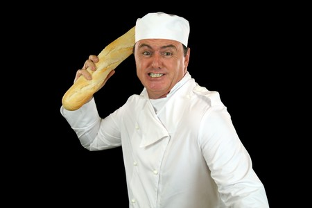 enraged: Furious and irate chef about to attack with a bread stick. Stock Photo