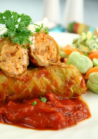Baked cabbage rolls with carrots and broad beans with a tomato sauce.
