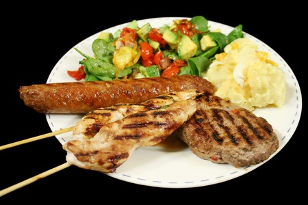 BBQ chicken tenderloin skewers, beef sausage, beef patty with spinach salad and potato salad. photo