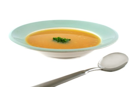 Profile view of pumpkin soup with parsley and spoon.
