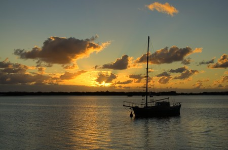 Sunrise breaks over classic old yacht in the still of the morning. Stock Photo - 4547306